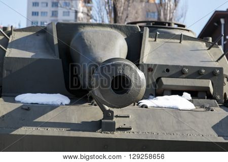 Green military armored tank, close up detailed view of old iron cannon ball.