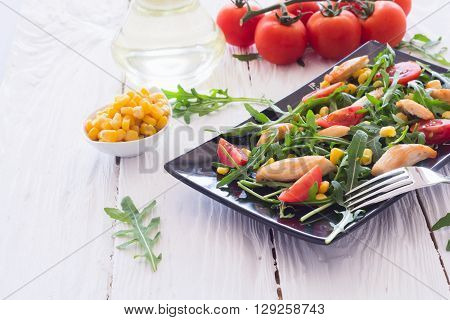 Fresh salad with arugula chicken and tomatoes on wooden background .