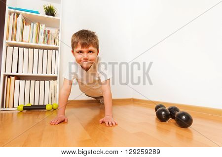 Push-ups or press-ups exercises by preschooler boy working out on the floor, strength training against a white wall with copyspace