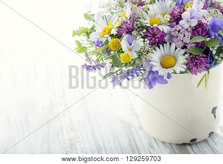 Wild flower bouquet on white vintage wooden background