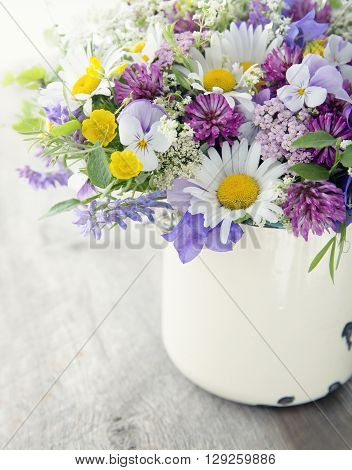 Wild flower bouquet on vintage wooden background