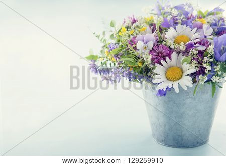 Wild flower bouquet on light blue vintage background