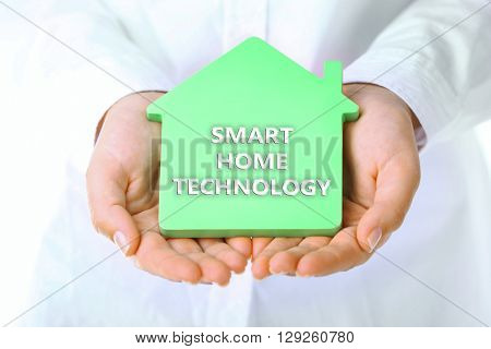 Smart home technology concept. Female hands holding house, closeup