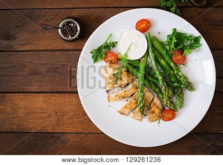 Baked Chicken Garnished With Asparagus And Tomatoes. Top View
