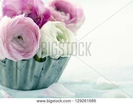Pink ranunculus flowers in a metal tin cup
