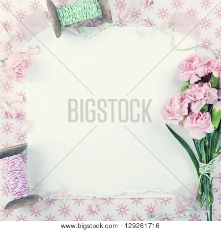 Pink floral background with a bouquet of carnations and hazy vintage editing