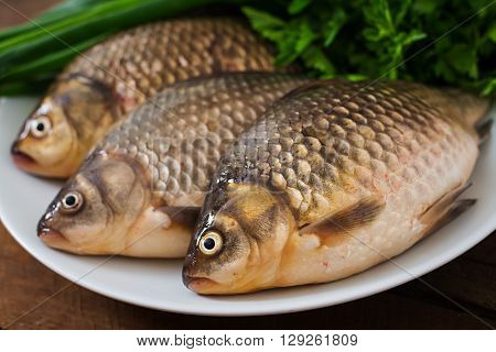 Three Fresh Raw Crucian On A Wooden Background With Herbs