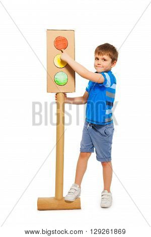 Cute boy pointing to red signal of handmade cardboard model of traffic light, isolated on white