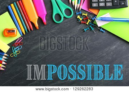 Word impossible transformed into possible on blackboard and school supplies