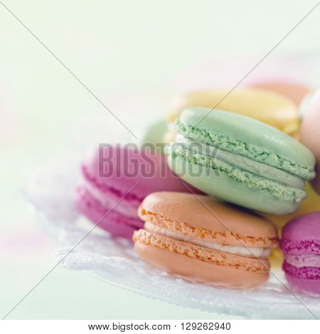 Colorful macarons on a tray with hazy pastel vintage editing