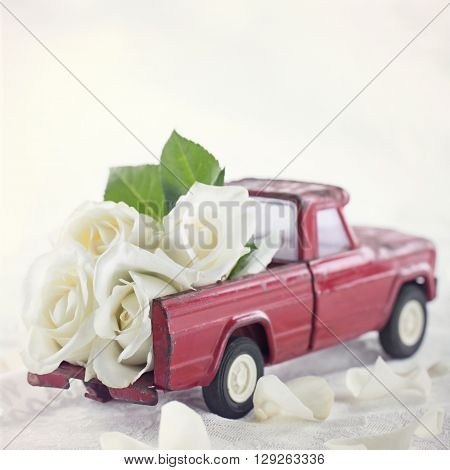 Red toy truck with white roses and romantic wedding background