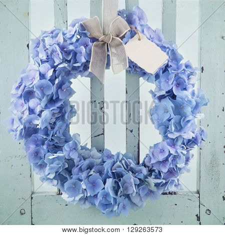 Blue hydrangea flower wreath on vintage wooden bakcground with a blank greeting card