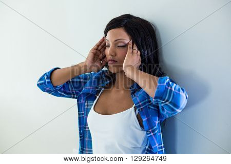 Tensed woman leaning on wall at home