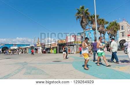 Venice Beach, USA - October 6, 2015: Tourists stroll boardwalk  in front the tacky shops and cheap signs under bright blue Californian sky Venice Beach California California