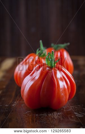 Fresh beef tomatoes on wooden table