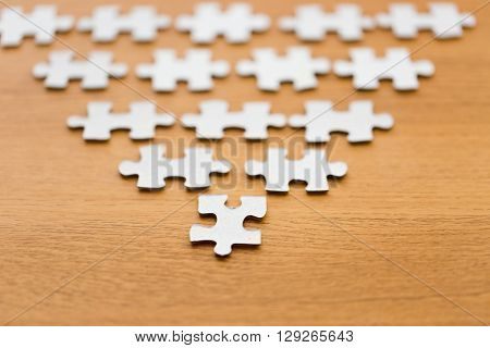 business and connection concept - close up of puzzle pieces in pyramid shape on wooden surface