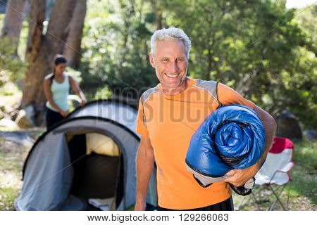 Man smiling and holding a sleeping bag on a camp site