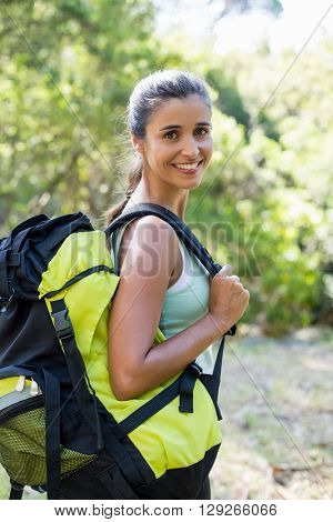 Woman smiling and posing with her backpack on the wood