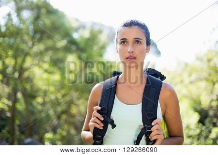 Woman unsmiling posing with her backpack on the wood