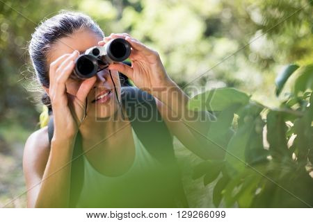 Woman looking something with binoculars on the wood