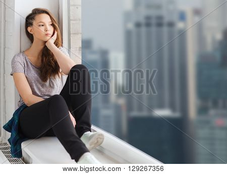 people, emotion and teens concept - sad unhappy pretty teenage girl sitting on windowsill and looking through window over singapore city skyscrapers background