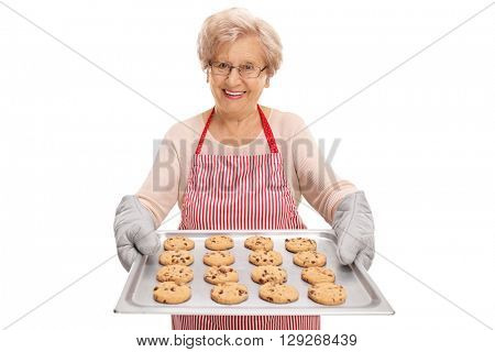Mature lady handing a tray full of chocolate chip cookies and smiling isolated on white background