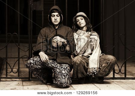 Young fashion hippie couple sitting on city street at the cast iron fence. Male and female fashion model outdoor
