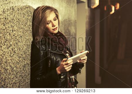 Young fashion woman using tablet computer at the wall. Female fashion model in black leather jacket