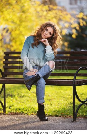 Happy young fashion woman with long curly hairs sitting on bench in city park. Female fashion model in ripped jeans outdoor