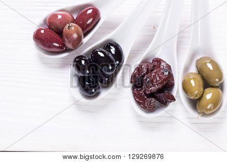 bowls with kind of olives green olives, black olives, pink olives