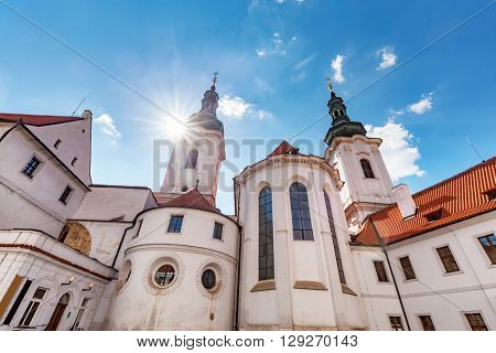 The Basilica of the Assumption of Our Lady in Strahov Monastery, Prague, Czech Republic. Sun shining on blue sky.