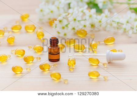 brown bottle with neroli essential oils and a pipette, gold capsules of natural cosmetic and flowers blossom on the wooden background