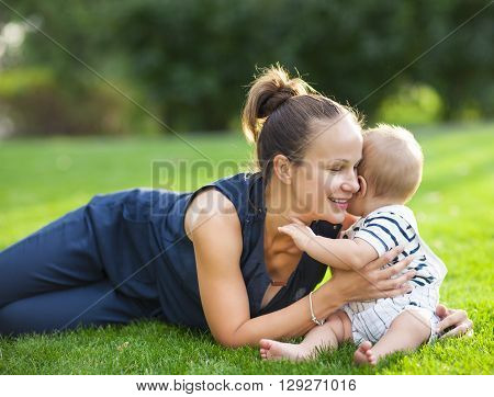 Happy mum and her child playing in park together. Outdoor portrait of happy family