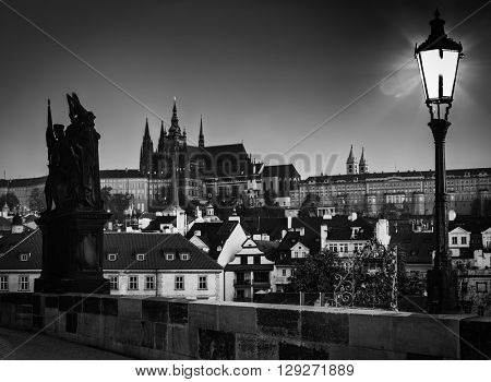 Charles Bridge at sunrise, Prague, Czech Republic. Dramatic statue and view on Prague Castle with St. Vitus Cathedral. Black and white