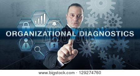 Corporate consultant is pressing ORGANIZATIONAL DIAGNOSTICS on an interactive touch screen. Business concept for analysis of an organizational system data collection and feed back on its processes.