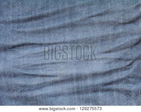 Crumpled dark rinse wash denim fabric background
