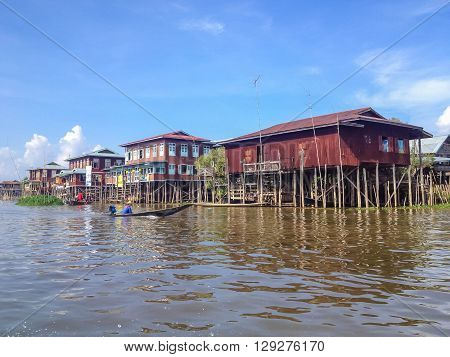INLE LAKE SHAN MYANMAR - MAY 26 : Wooden stilt houses and passenger boat at Inle lake Myanmar on May 26 2014