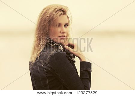 Young blond woman walking in a fog. Female fashion model in denim jacket outdoor