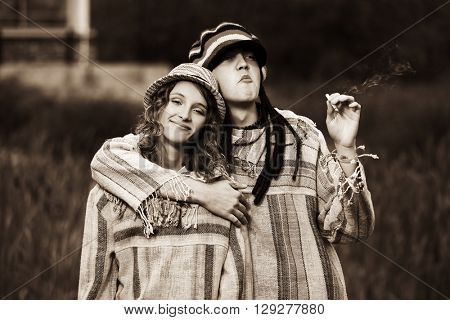 Young hippie couple walking in love. Male and female fashion model outdoor. Young man and woman in park