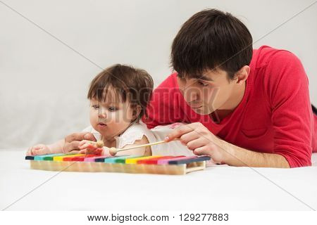 Father and baby girl playing xylophone toy on blanket at home