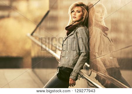 Young fashion blond woman standing at the wall. Female fashion model outdoor