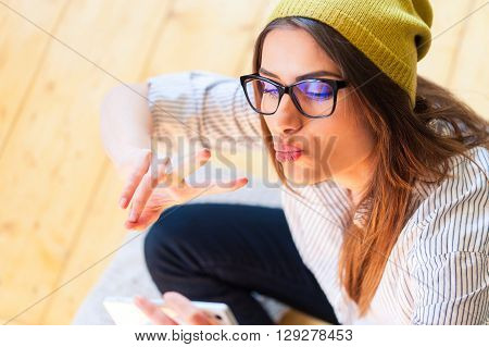 Pretty hipster girl taking selfie and making duck face, sending kisses, holding peace sign