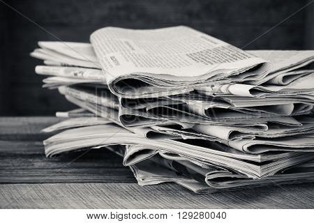 Newspapers and magazines on old wood background. Black and white shot.