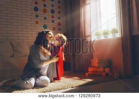 Happy loving family. Mother and her child girl playing together. Girl in an Superman's costume.