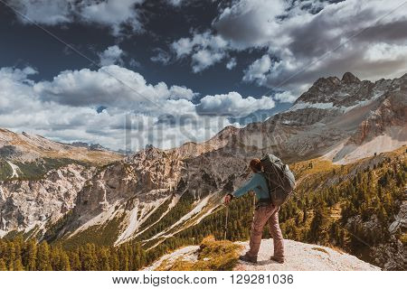 Female hiker with backpack standing on top in Dolomites mountains