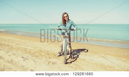 Beautiful girl in glasses standing with bicycle on sand beach on background of sea in summer