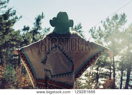 Happy fashionable young woman wearing in poncho and hat standing with raised arms in summer pine forest and enjoying a nice day rear view