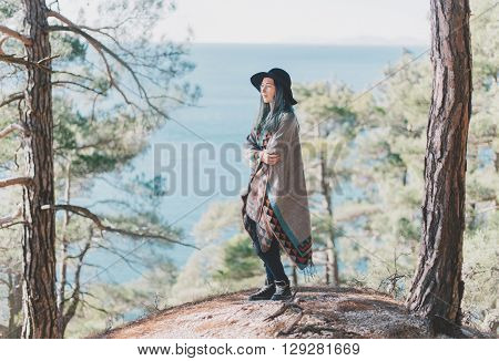 Beautiful young woman wearing in poncho and hat standing among pine trees in the summer forest on background of sea