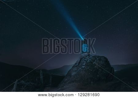 Traveler woman sitting on peak of rock and looking at starry sky light beam in the night sky. Concept of dream and explore