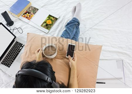 Top view Asian girl sitting on bed surfing internet on mobile phone drinking hot coffee and listening to music with wireless headphone in relax mood with blank note book and things around for background